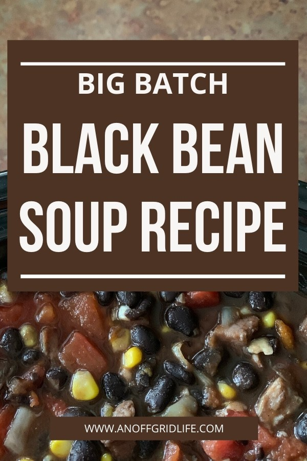 Big batch black bean soup recipe text overlay on bean soup in black pot with chunks of ham and tomatoes
