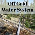 Off Grid Water System text overlay on image of outdoor water pipe leading down to a lake.