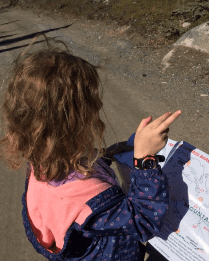 Child trying to read a map outdoors