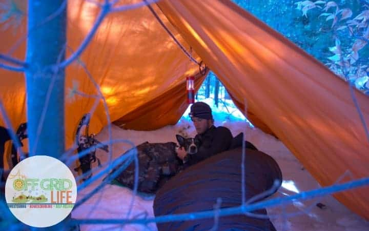 Young man winter camping in tent