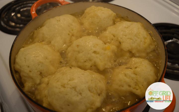 dumplings steaming on top of a rabbit stew