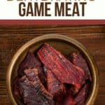 """a pinterest picture of a can of beef jerky on a wooden table with text overlay """"smoking and dehydrating game meat"""""""