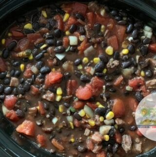 Big batch black bean soup recipe text overlay on pot of soup with chunky tomatoes, black beans and corn