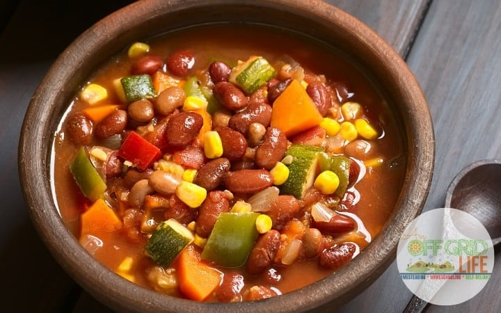 Bowl of three bean chili with vegetables including celery, peppers, carrots and corn