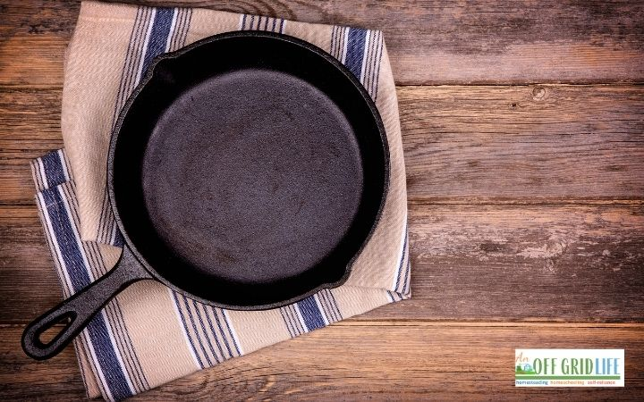 a picture of a single cast iron skillet on a blue and white wash cloth
