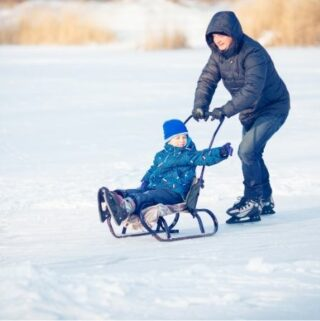 Parent skating on outdoor lake pushing child on a sled