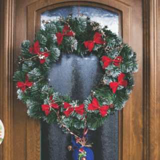 A green christmas wreath on a wooden door with a blue ornament.