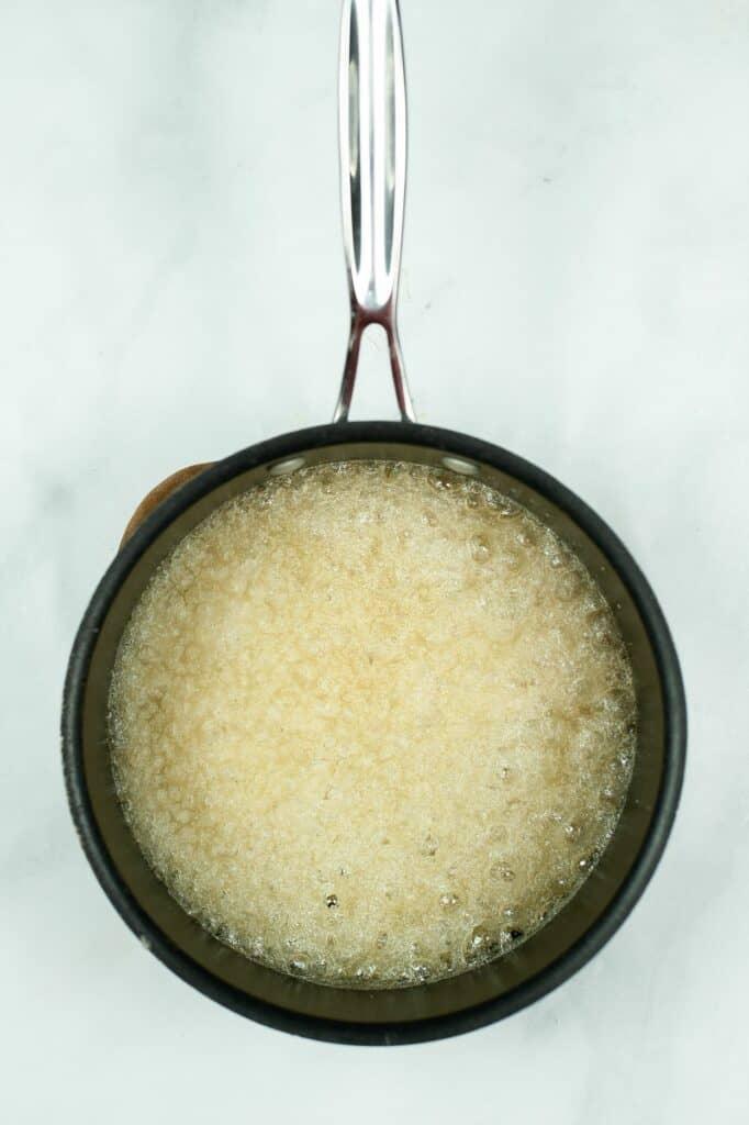Sugar and water boiling in saucepan