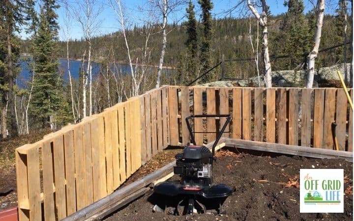 a picture of an electric garden tiller in a soil garden bed with a pallet fence surrounding it.