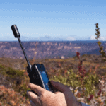 a picture of a man u sing a satellite phone in a field with blue skies