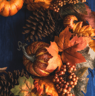 an orange and brown fall wreath on a dark blue wooden door.