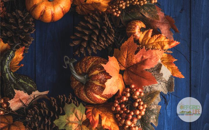 an orange and brown fall wreath on a dark blue wooden door.