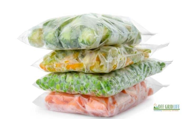 four stacks of ziploc bags filled with frozen vegetables