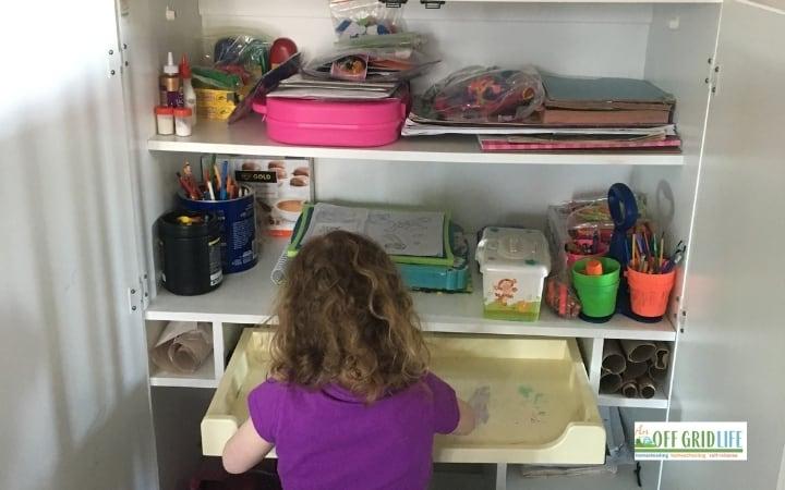 Child at homeschool shelving unit