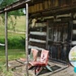 Rustic log cabin and front porch with two chairs - how much does it cost to move off the grid