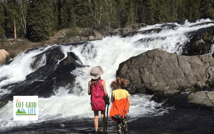 Two young girls looking at rapids by the side of large rocks in the springtime with knapsacks on their backs
