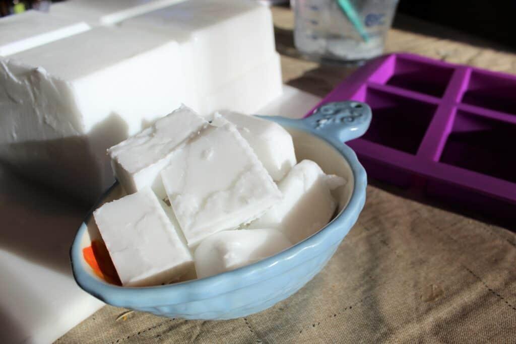 blocks of plain goat milk soap base in a blue bowl