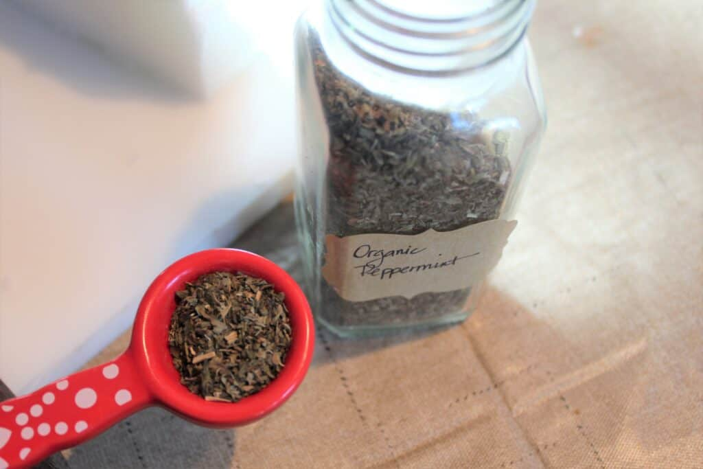 dried peppermint leaves in glass jar and red measuring spoon