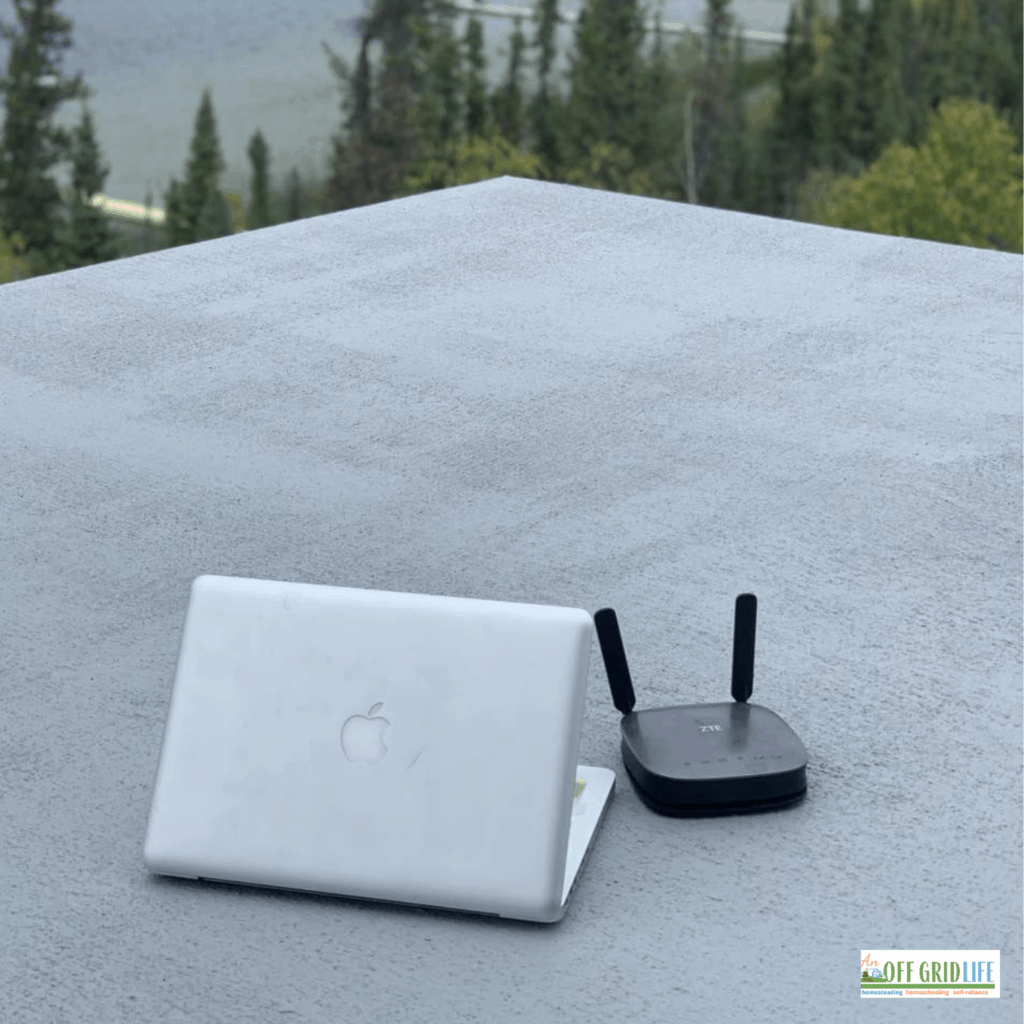 a laptop and router on a roof of an off grid cabin
