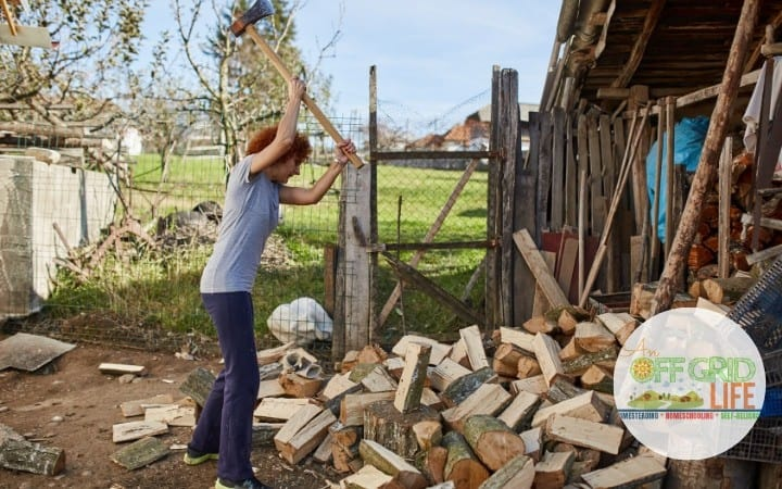 Woman chopping wood in a country yard