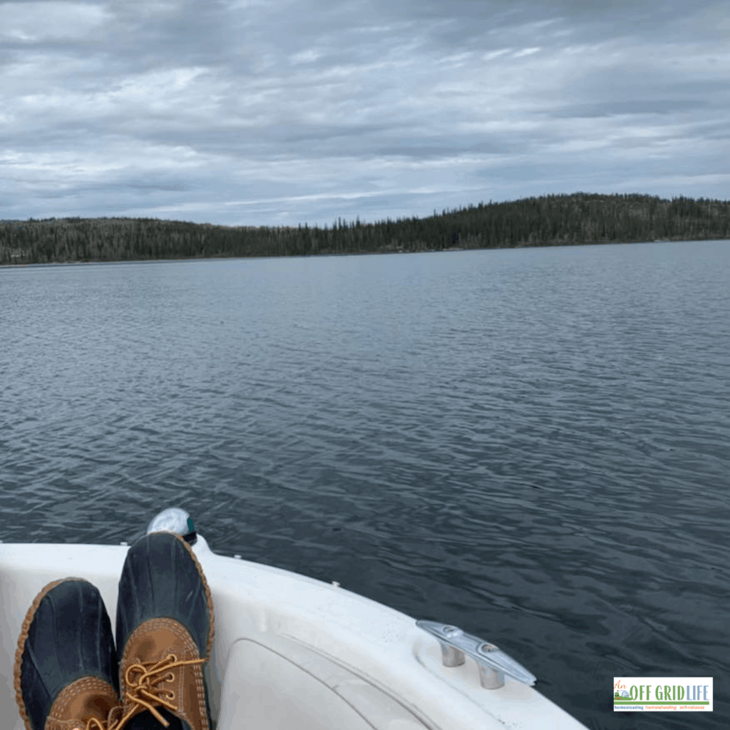 a picture off grid of someones feet up on a boat looking at open water.