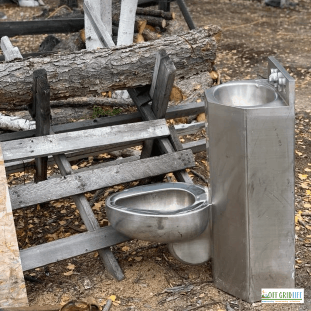 a stainless steel toilet and sink next to a wooden fence outdoors