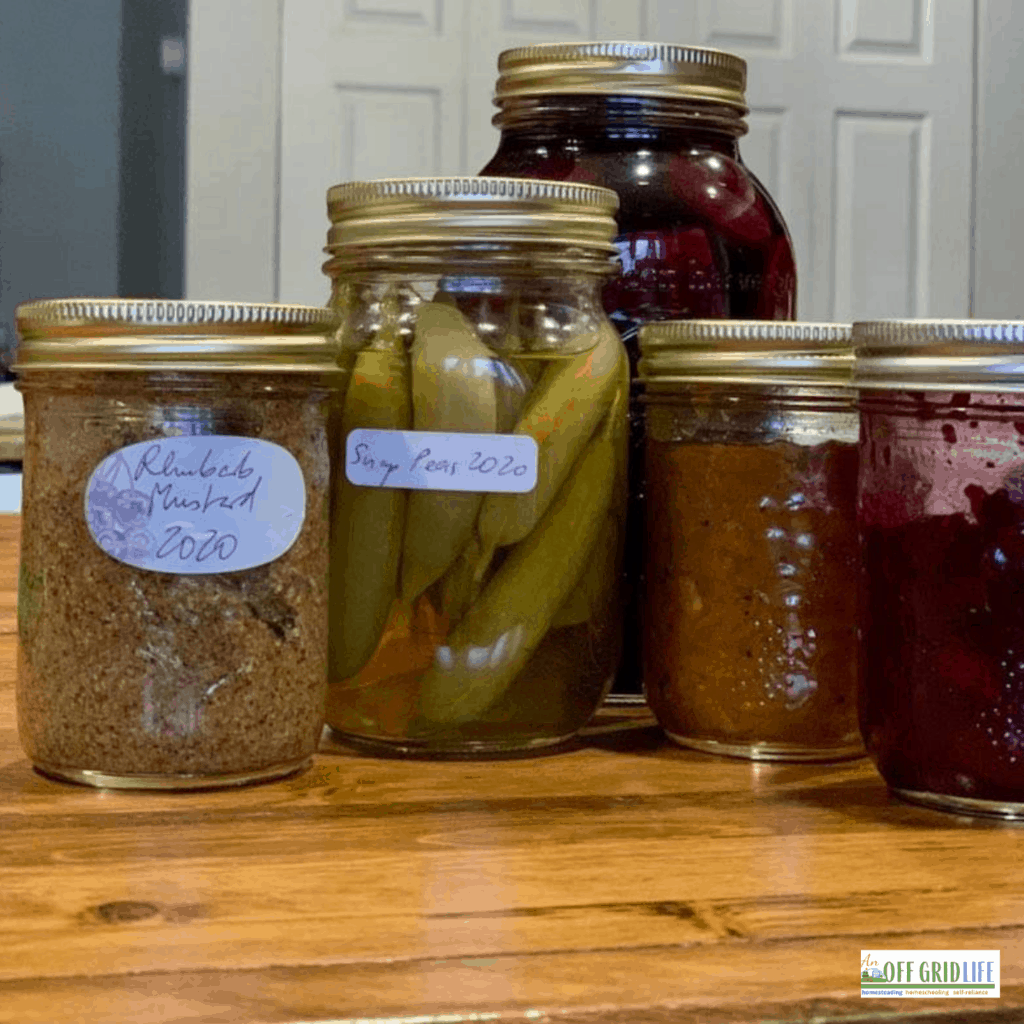 5 mason jars with pickled vegetables and preserves on a wooden counter