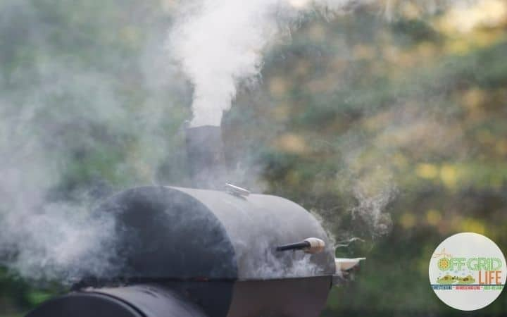 A black charcoal smoker with smoke coming out of the top dampener