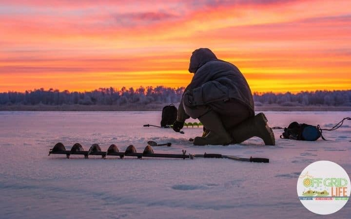 a person on a frozen lake with an ice auger drilling a hole for ice fishing