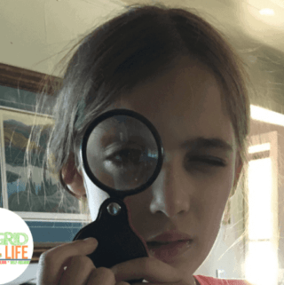 Young girl looking through magnifying glass directly at camera