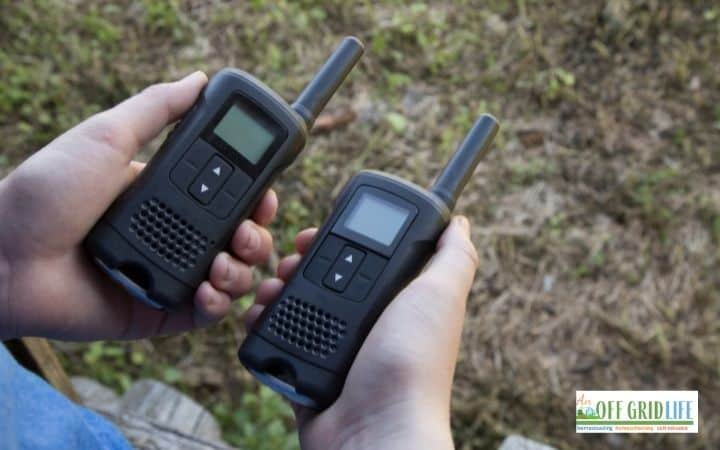 two hands each holding a small walkie-talkie outdoors.